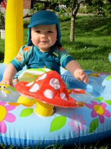 junior i solbeskyttende dragt i sit badebassin